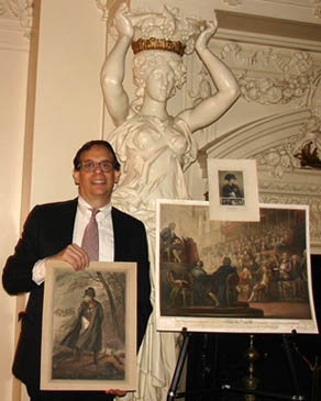 George holds a lithograph portrait of Napoleon from the 1820s. On the easel to his right is a large print of King Louis XVI's final address after being arrested by radicals during the French Revolution and a smaller portrait of Napoleon.