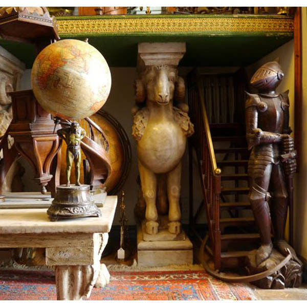 Marble winged ram figure, carved wooden knight, and globe supported by figure of Atlas